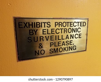 exhibits protected by electronic surveillance and please no smoking sign on yellow wall
