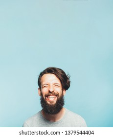Exhilarated bearded hipster. Happy young man toothy smile closed eyes. Strong feeling mood emotion facial expression. Free space