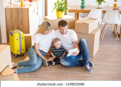 Exhited family with little toddler son are resting after moving into new apartment. They are using the digital table while sitting on the floor and surrounded by carboard boxes