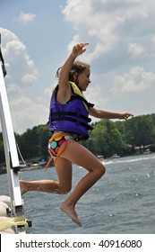an exhuberent little girl jumps off a boat into the water