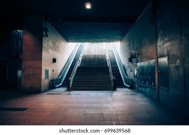 Exit with escalator from the underground metro. Light at the end of the tunnel concept