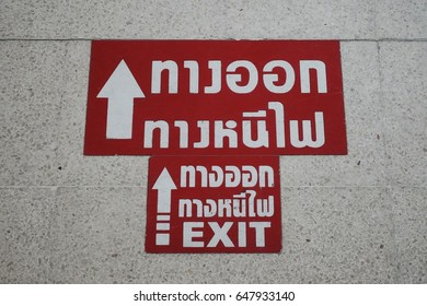 Exit and Fire Exit. Symbol to show the way for Fire Exit on the floor of Thai building (Thai language in image is 'Exit' and 'Fire Exit')