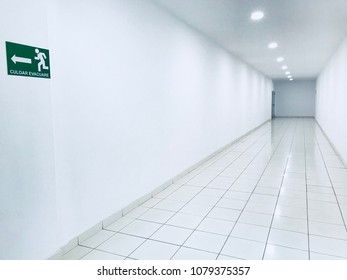Exit hallway/evacuation corridor perspective with white tiles, walls and white light spots, an exit sign in the foreground and a exit door in the far end of the hall.