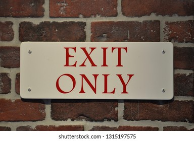 Exit only sign posted in a brick wall