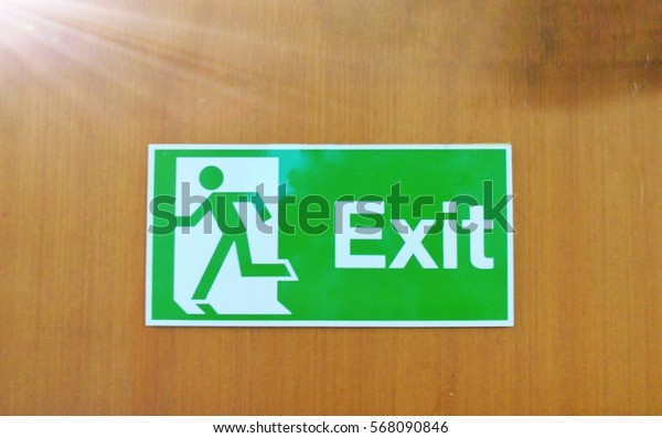 Exit sign on wooden wall background. Artificial light was added on the top left corner.