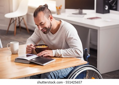 Exited handicapped guy eating cereal in the morning