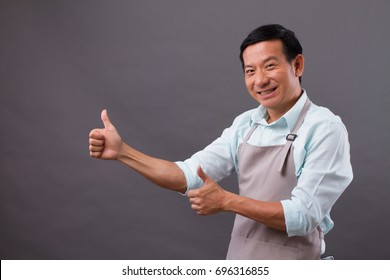 exited man shopkeeper pointing thumb up to space, concept of small business owner, shop manager, entrepreneur suggesting something