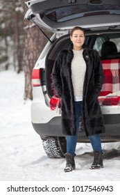 Exited young Caucasian woman in unbutton mink fur stands full-length near own car. Walking in winter forest