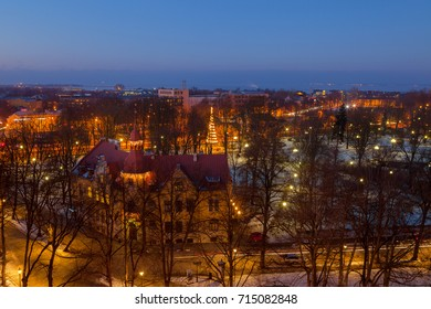 Exiting winter view of night old town of Tallinn. Aerial over park with sea.