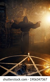 Exorcist in hood reads spell near the magic circle