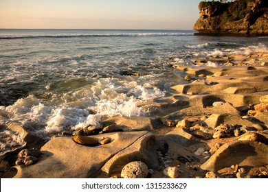Exotic Balangan beach shore. Sunset view. Bali. Indonesia. Close-up sunlit sand boulders. Geological activity of the ocean, erosion of the ocean shore. Ideal background for collages and illustrations.