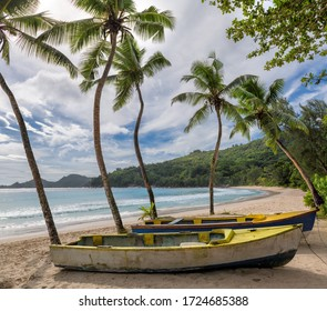 Exotic beach with coco palm trees and a fishing boats in the turquoise sea on Tropical island.