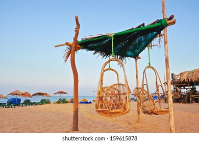 Exotic beach umbrellas and rocking chairs on tropical coast in Goa