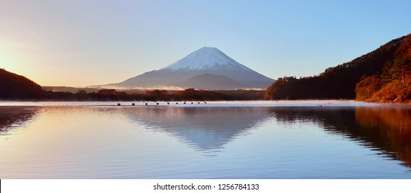 The Exotic beautiful peaceful panorama landscape scene in the morning of Fuji Mountain, the famous landmark of Japan, make a great reflection into Shojiko lake. the sun are rising behind the mountain.
