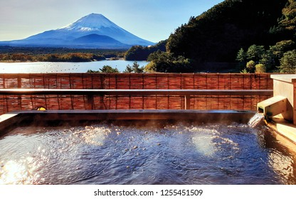 The Exotic beautiful peaceful scene of Onsen, japanese hot tub in the morning. background is Fuji Mountain, the famous landmark of Japan, at Shojiko lake, see many bubbles from very hot water in tub.