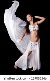 An exotic, brunette bellydancer dances with a flowing, white silk veil. Isolated on a black background. Clipping path included.