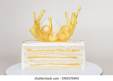 Exotic cake cutaway with white chocolate spheres and caramel splash decorated with candurin