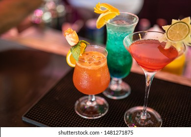 Exotic cocktails, mojito-cocktail, orange cocktail, strawberry cocktail in glass glasses with straws and fruits and blurred bar accessories: shaker, spoon, spices Colorful cocktails on the bar counter