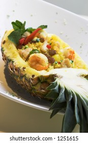 An exotic dish of seafood fried rice inside a pineapple shell. The scattering of fine pieces around the dish is a part of the stylish of the dish.