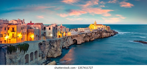 Exotic evening cityscape of Vieste - coastal town in Gargano National Park, Italy, Europe. Coloful spring sunset on Adriatic sea. Traveling concept background.