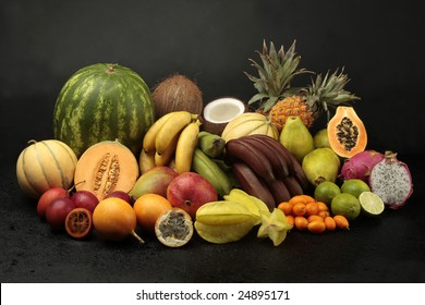 Exotic fruit arrangement on black background with water drops