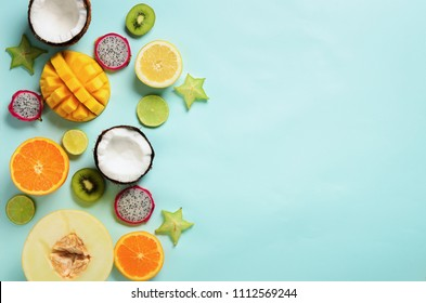 Exotic fruits on pastel blue background - papaya, mango, pineapple, banana, carambola, dragon fruit, kiwi, lemon, orange, melon, coconut, lime. Top view