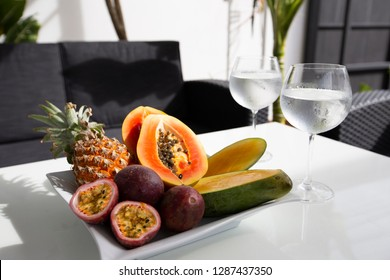 Exotic fruits on a plate with two glass of cold water