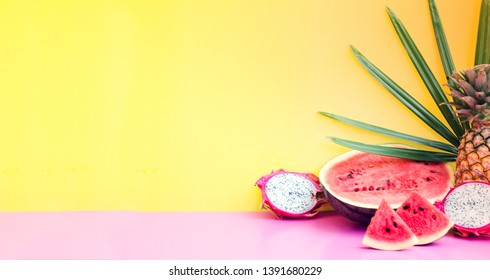 Exotic fruits and tropical palm leaves on pastel background