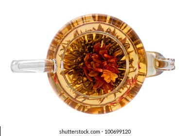 exotic green tea with flowers in glass teapot isolated on white (top view)