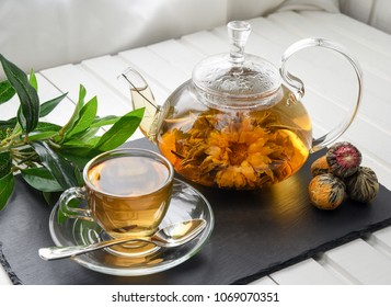 Exotic green tea with flowers in glass teapot.