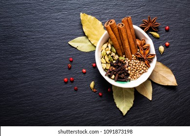 Exotic herbal Food concept Mix of the organic Spices cinnamon stick, cardamom pods, bay leaves, star anise and coriander seeds in white ceramic cup on a black slate stone plate with copy