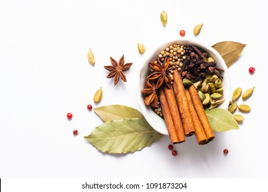 Exotic herbal Food concept Mix of the organic Spices cinnamon stick, cardamom pods, bay leaves, star anise and coriander seedsin white ceramic cup on white background