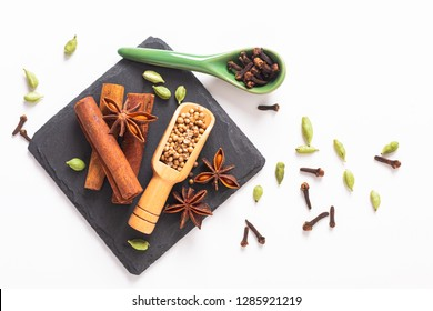 Exotic herbal Food concept Mix of the organic Spices cinnamon stick, cardamom pods, star anise and coriander seeds on a black slate stone plate with copy