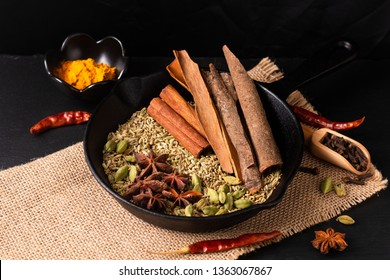 Exotic herbal Food concept Mix of the organic Spices cinnamon stick, cardamom pods, cloves, star anise and fennel seeds in slilet cast on a black slate stone plate with copy