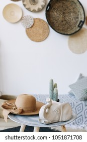 Exotic interior. Summer hat, cactus and elephant figurine on table indoors. Interior design elements. Flat lay, top view
