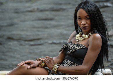 Exotic looking African American woman posing in front of camera wearing black mini dress and jewellery with pearls.