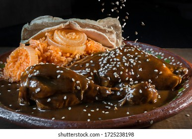 Exotic Mexican food on a mud or clay plate. Chicken Mole from Oaxaca with sesame seeds falling from above and  a side of Mexican tomato rice and corn tortillas in a black background and a wooden table