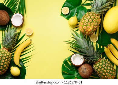 Exotic pineapples, ripe coconuts, banana, melon, lemon, tropical palm and green monstera leaves on yellow background with copyspace. Creative layout. Monochrome summer concept. Flat lay, top view