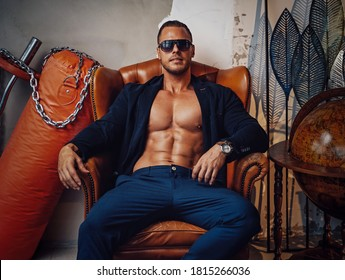 Exotic room with sportive and luxurious stuffs and muscular macho with naked torso which sitting on armchair.