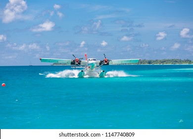Exotic scene with seaplane on Maldives sea landing. Vacation or holiday in Maldives concept background