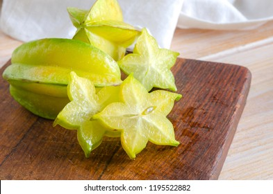 Exotic starfruit or averrhoa carambola on wooden cut board. Perfect ingredient for healthy food, vegetarian or vegan diet