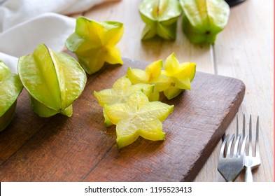 Exotic starfruit or averrhoa carambola on wooden cut board. Healthy food, fresh organic star apple fruit. Carambola background.