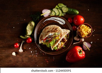 Exotic still slife with stuffed pita and fresh vegetables over wooden background, selective focus.