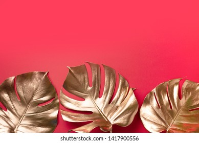 Exotic summer trend in minimal style. Golden tropical palm monstera leaf on red color background. Shiny and sparkle design, fashion concept