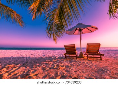 Exotic tropical beach sunset, colorful landscape for background or wallpaper. Romantic beach scene with chairs and soft sand. Design of tourism for summer vacation holiday destination concept.