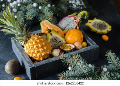 Exotic, tropical fruits in a basket - grenadilla, rambutan, passion fruit, kumquat, tamarind, pineapple, dad, wooden background. Christmas present - fruit box.