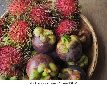 Exotic and tropical fruits: Mangosteens and Rambutans from Thailand. In basket on wooden surface.