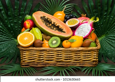 Exotic tropical fruits in wicker basket on palm leaves and wooden background, healthy food, diet nutrition