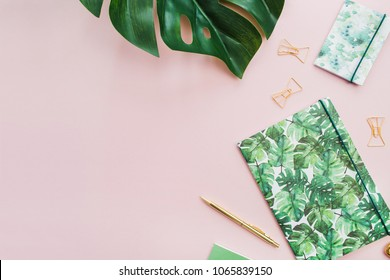 Exotic tropical monstera palm leaf and home office stationery on pale pink background. Flat lay, top view minimal workspace.