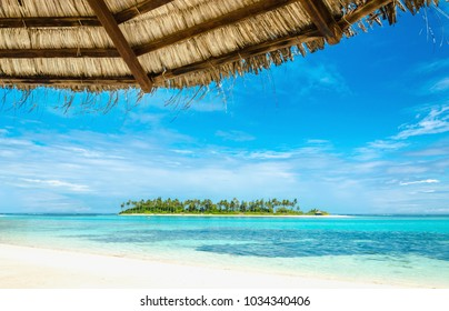 Exotic uninhabited island with a sandy beach and tall palm trees with a palm tree umbrella in the foreground